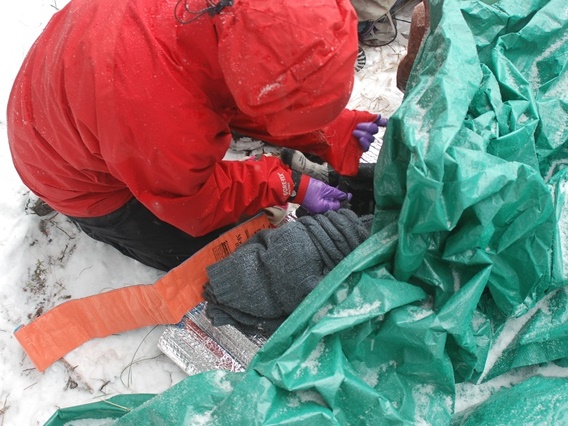 A Wilderness First Responder student builds a splint in the snow.